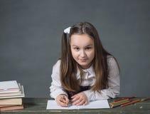 坐在与书的一张桌上的校服的女婴 免版税库存图片