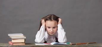 坐在与书的一张桌上的校服的女婴 免版税库存照片