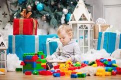 坐在与书的圣诞树的逗人喜爱的男孩 免版税库存图片