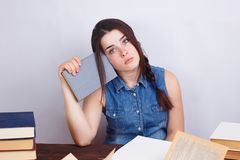 坐在与书的桌上的年轻疲乏的乏味学生妇女 免版税图库摄影