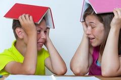 坐在与书的桌上的母亲和儿子 免版税库存照片