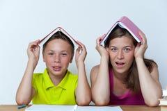 坐在与书的桌上的母亲和儿子 库存图片