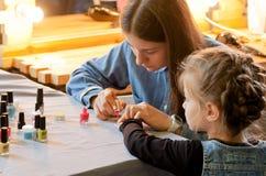 坐在与五颜六色的钉子的修指甲大师附近的未认出的孩子在孩子空间 库存照片