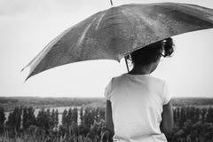 坐在与伞的倾吐的雨中的女孩 免版税库存照片