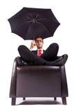 坐在与伞的方便的扶手椅子的人 免版税库存照片