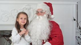 坐在与作梦关于她的圣诞节礼物的一个小女孩的一把椅子的圣诞老人 库存照片