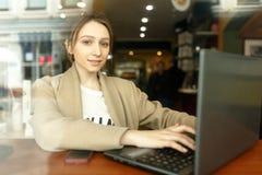 坐在与便携式计算机的一张咖啡馆桌上的女孩 免版税库存照片