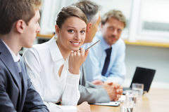 坐在与同事的一个业务会议上的微笑的妇女 图库摄影