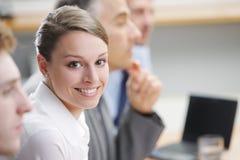 坐在与同事的一个业务会议上的微笑的妇女 免版税图库摄影