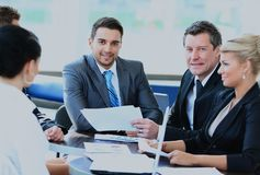 坐在与同事的一个业务会议上的微笑的年轻人 免版税库存图片