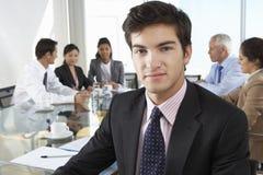 坐在与同事的会议室表附近的商人 免版税图库摄影