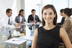 坐在与同事的会议室表附近的女实业家 图库摄影