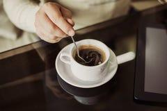 坐在与咖啡的一个咖啡馆的年轻成功的人 库存图片