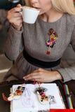 坐在与咖啡的咖啡馆的美丽的白肤金发的女孩和蛋糕工作和画在笔记本的剪影 库存照片