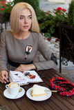 坐在与咖啡的咖啡馆的美丽的白肤金发的女孩和蛋糕工作和画在笔记本的剪影 库存图片