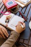 坐在与咖啡的咖啡馆的美丽的白肤金发的女孩和蛋糕工作和画在笔记本的剪影 免版税库存图片