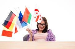 坐在与国际旗子的桌上的愉快的少妇 免版税图库摄影