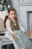 坐在与圣诞节礼物的一把椅子的小女孩在手 库存图片