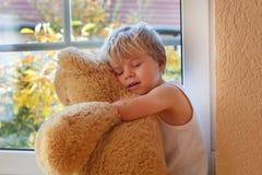 坐在与大玩具熊的窗口附近的两年的可爱的男孩。 免版税库存照片