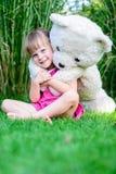坐在与大玩具熊的草的小逗人喜爱的女孩 免版税图库摄影