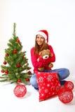 坐在与女用连杉衬裤b的一棵圣诞树附近的微笑的小女孩 库存图片