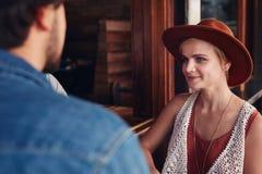 坐在与她的朋友的一个咖啡馆的美丽的少妇 免版税图库摄影