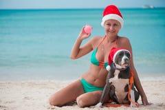 坐在与她的朋友amstaff狗的海滩的圣诞节帽子的年轻愉快的妇女 免版税图库摄影