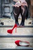 坐在与她的鞋子的步的未知的妇女 免版税库存照片