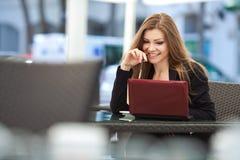 坐在与室外的膝上型计算机的一个咖啡馆的美丽的微笑的妇女画象  库存照片