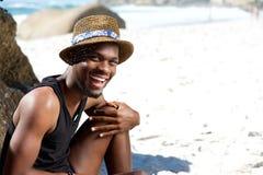坐在与帽子的海滩的愉快的人 免版税库存照片