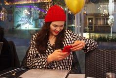 坐在与手机的一个咖啡馆的女孩 库存图片
