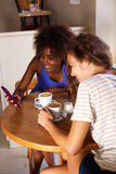 坐在与手机的咖啡馆的两个女朋友 免版税库存图片