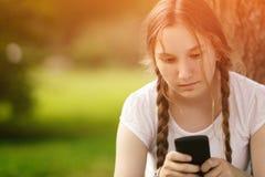 坐在与手机的树附近的青少年的女孩 库存照片