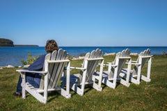 坐在与拷贝空间的海滩睡椅的妇女 免版税图库摄影