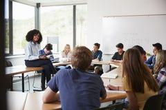 坐在与教算术课的学生的表上的女性高中家庭教师 库存照片