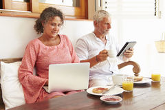 坐在与数字式设备的早餐桌上的成熟夫妇 免版税图库摄影