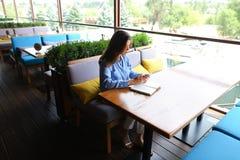 坐在与智能手机的咖啡馆和写下在日志的女孩 库存照片