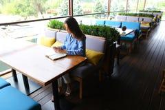 坐在与智能手机的咖啡馆和写下在日志的女孩 免版税库存照片