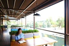 坐在与智能手机的咖啡馆和写下在日志的白种人女孩 库存照片