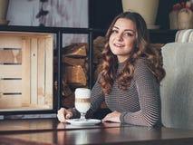 坐在与杯子的意大利样式咖啡馆的美丽的少妇  免版税库存照片