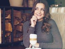 坐在与杯子的意大利样式咖啡馆的美丽的少妇  库存图片