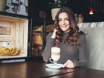 坐在与杯子的意大利样式咖啡馆的美丽的少妇  免版税图库摄影