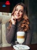 坐在与杯子的意大利样式咖啡馆的美丽的少妇  库存照片