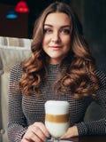 坐在与杯子的意大利样式咖啡馆的美丽的少妇  免版税库存图片