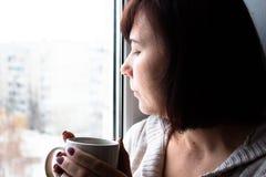 坐在与杯子的窗口附近的妇女 免版税库存图片