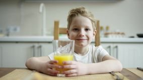 坐在与杯的午餐期间的高兴的男孩橙汁过去和等待的款待与流动的照相机 股票视频