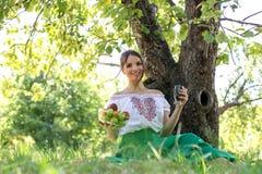 坐在与果子和energii玻璃板材的一棵树下的美丽的少妇  免版税图库摄影