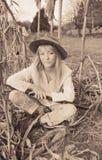 坐在与枪的麦地的美丽的妇女 库存图片
