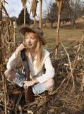 坐在与枪的麦地的美丽的妇女 库存照片