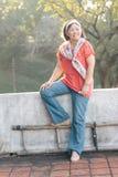 坐在与树的日落期间的愉快的妇女模型姿势在背景中 免版税库存图片